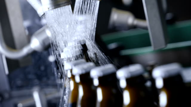 beer bottling line, cleaning bottles in slow motion - attrezzatura industriale video stock e b–roll