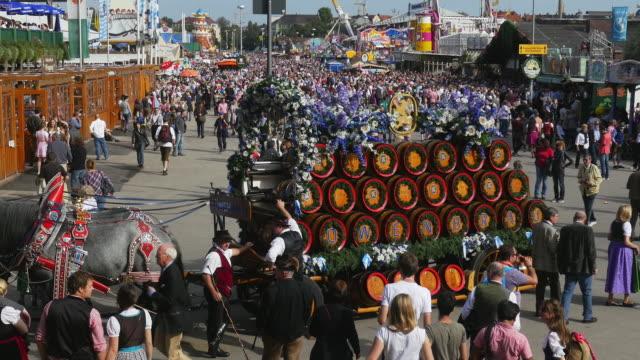 beer carriage on oktoberfest fairgrounds (4k/uhd to hd) - stahlfass stock-videos und b-roll-filmmaterial