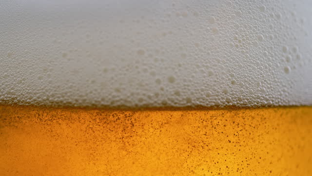 slo mo ld beer foam moving in a glass - frothy drink stock videos & royalty-free footage