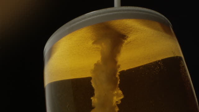 beer froth pouring into a glass with golden background shot on red epic - amber stock videos & royalty-free footage