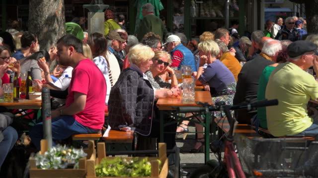 beer garden at viktualienmarkt, munich, bavaria, germany - ハッピーアワー点の映像素材/bロール