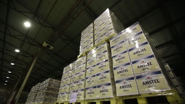 Beer kegs sit stacked on pallets next to shrinkwrapped cases containing bottles of Heineken lager and Amstel Weiss beer inside the warehouse at the...