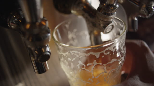 beer pouring from a tap slowly fills a pint glass with amber colored beer and a foam head. - pint stock-videos und b-roll-filmmaterial