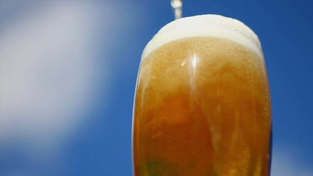 la cu  beer pouring into glass in front of blue sky - pint glass stock videos & royalty-free footage