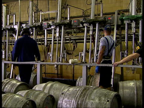 stockvideo's en b-roll-footage met england london wandsworth ext beer barrels being moved into position beneath taps to be filled with beer in factory/ beer barrels lined up in room/... - wandsworth