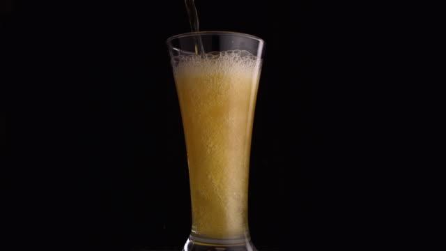 vídeos de stock e filmes b-roll de cu slo mo beer swirling in pilsner glass / studio, new jersey, usa - studio shot