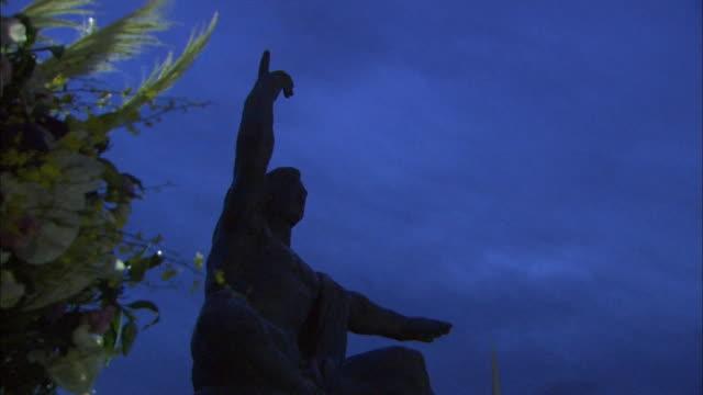 before daybreak on the 69th atomicbomb day of nagasaki low angle shot of flowers offered to abomb victims silhouette of the peace statue in background - massförstörelsevapen bildbanksvideor och videomaterial från bakom kulisserna