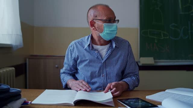 vor jeder klasse bereitet sich ein fleißiger lehrer auf ein pädagogisches fach vor, damit er alle antworten für seine schüler haben kann. - content stock-videos und b-roll-filmmaterial