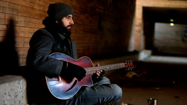 beggar playing guitar on the street - begging social issue stock videos and b-roll footage