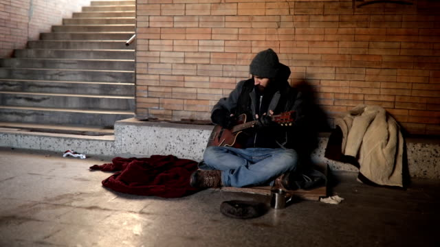 beggar playing guitar on the street - musicista video stock e b–roll