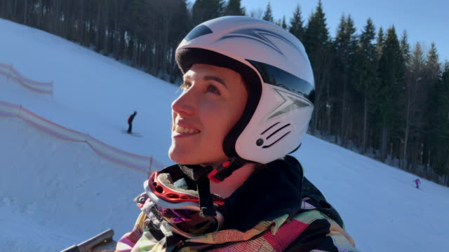 Beginner skier sitting on the ski lift while going to the top of piste