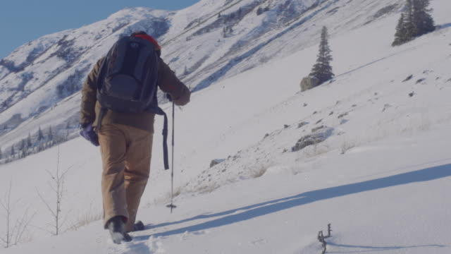 beginning of a long hike to the top of a mountain - cappotto invernale video stock e b–roll