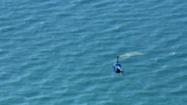 aerial behind a helicopter flying above the sea on a sunny day - helicopter stock videos & royalty-free footage