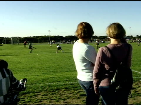 behind backs of several caucasian females mothers watching high school field hockey day game 1st team in white amp grey uniforms 2nd team wearing... - field hockey stock videos and b-roll footage