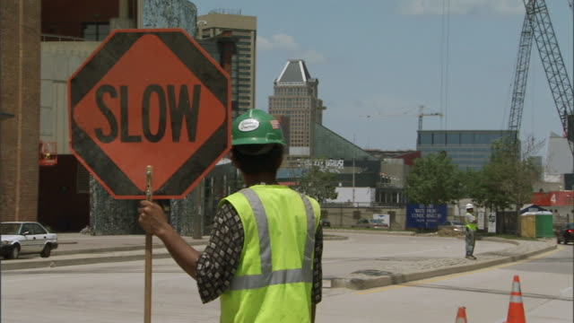 behind brown skin male construction worker in hard hat standing in street holding slow sign, another worker on median, no traffic, commerce place... - median nerve stock videos & royalty-free footage