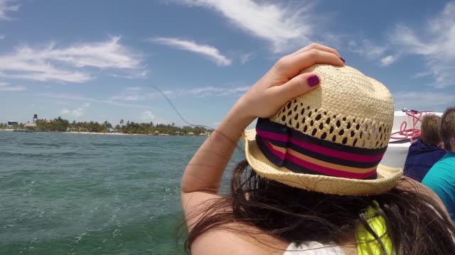POV behind female on a boat cruising the Caribbean Sea