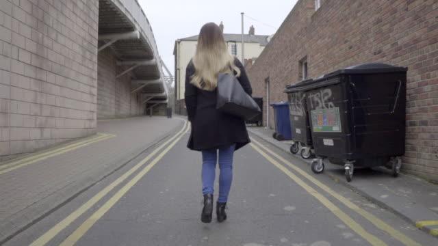 behind following smart casual attractive blonde woman black winter coat walking - winter coat stock videos & royalty-free footage