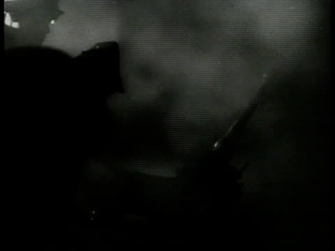 german soldiers firing antiaircraft guns against lighted smoke bg flak barrage ws searchlights scanning sky antiaircraft firing night sky explosions... - luftvärn bildbanksvideor och videomaterial från bakom kulisserna