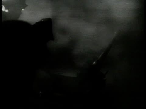 German soldiers firing antiaircraft guns against lighted smoke BG flak barrage WS Searchlights scanning sky Antiaircraft firing night sky explosions...