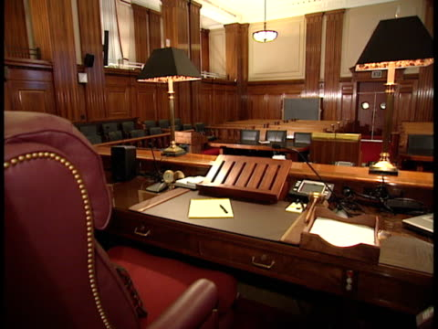 empty judge's bench & table w/ paper, pen, equipment, empty courtroom, jury box , tables, & gallery bg. honorable, law, trial. - court room stock videos & royalty-free footage