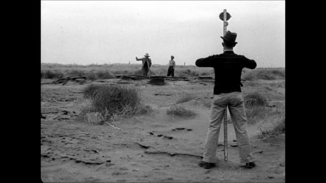 surveyor measuring scrub land men putting up 'soil conservation service' sign on fence vs men plowing hilltop walking behind team of horses along top... - dust bowl stock videos and b-roll footage