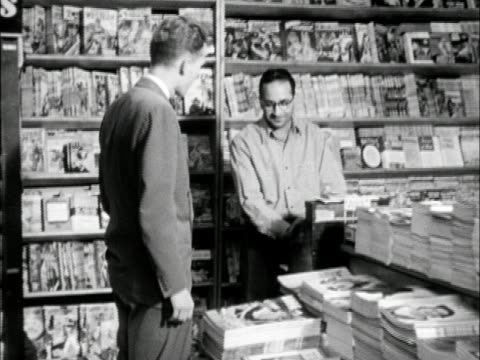 dramatization behind male in magazine store being greeted by clerk handing male special issue of 'life magazine' about us schools w/ rue lawrence... - magazine publication stock-videos und b-roll-filmmaterial
