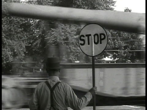 behind male railroad gateman in hat suspenders standing by train track holding stop sign w/ train passing fast bg. - suspenders stock videos & royalty-free footage