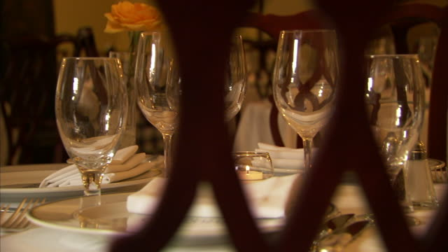 fine dining room table fully set w/ table cloth single rose votive candle water goblets wine glasses folded cloth napkins on plates dolly behind... - votive candle stock videos and b-roll footage