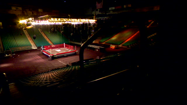 behind silhouetted pillars amp stair railing ls empty lighted arena amp boxing ring w/ overhead spotlights amp colored seating lighting on dolly - ボクシングリング点の映像素材/bロール