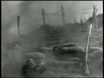 soldier throwing grenade from other side of barbed-wire fencing grenade exploding fg. machine gun firing. soldiers advancing hill. graphic: bodies of... - 1936 stock videos & royalty-free footage