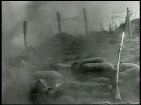 stockvideo's en b-roll-footage met soldier throwing grenade from other side of barbed-wire fencing grenade exploding fg. machine gun firing. soldiers advancing hill. graphic: bodies of... - 1936