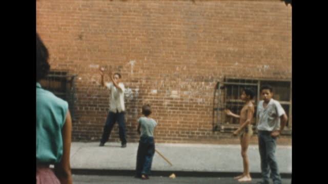 behind the back shot of a group of kids playing stickball/baseball in new york's lower east side. a girl pitches the ball and the boy swings and... - messing about stock videos & royalty-free footage
