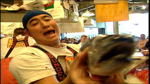 behind the counter at pike place fish market men throwing fish in seattle washington - pike place market stock videos and b-roll footage