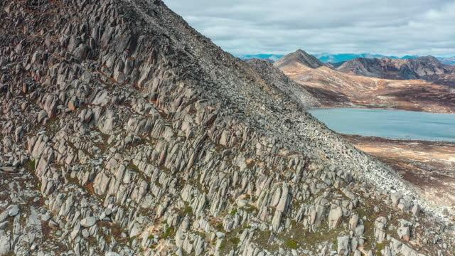 stockvideo's en b-roll-footage met achter de enorme granieten berg ligt een rustig meer - kei