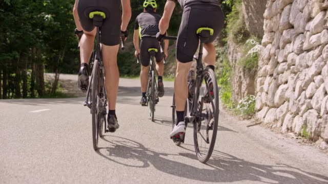 slo mo behind three road cyclists training on a mountain road - cycling helmet stock videos & royalty-free footage