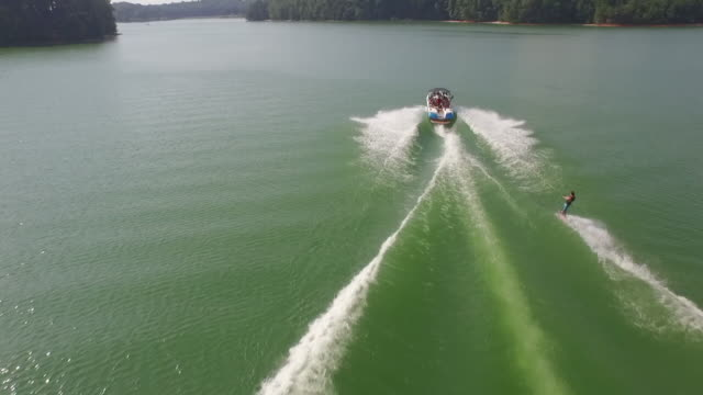 behind tracking wakeboarding doing tricks - drone aerial video 4k wakeboard, wake surfing and wake skating on georgia lake on beautiful water extreme action sports, front flip, backflip, twist and wipeout tracking reveal 4k sports - wakeboarding stock videos and b-roll footage