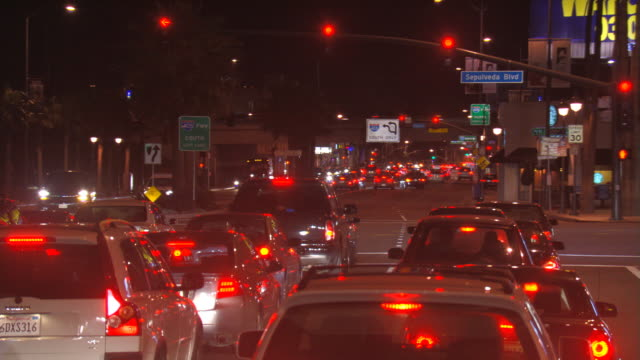 behind traffic at sepulveda boulevard signal in los angeles at night; driver's pov - artbeats stock videos & royalty-free footage