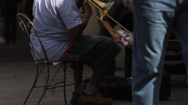behind unidentifiable man dressed in warm weather clothing sitting on chair on sidewalk playing trombone person walking by dropping money into bag... - brass instrument stock videos & royalty-free footage