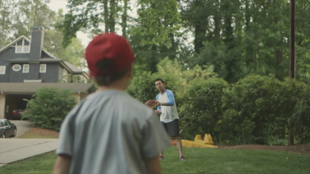 Behind view of boy playing catch