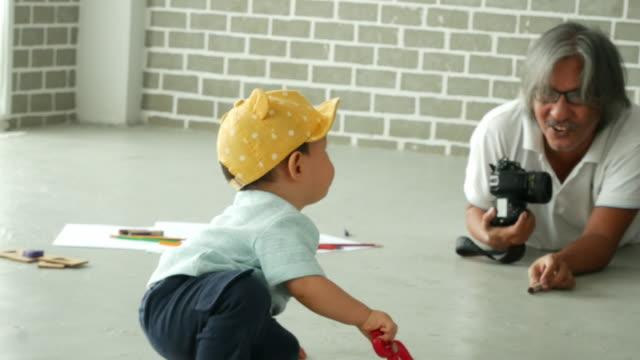 シーンをベヒネ、祖父は彼の甥の写真を撮影しようとします - 甥点の映像素材/bロール