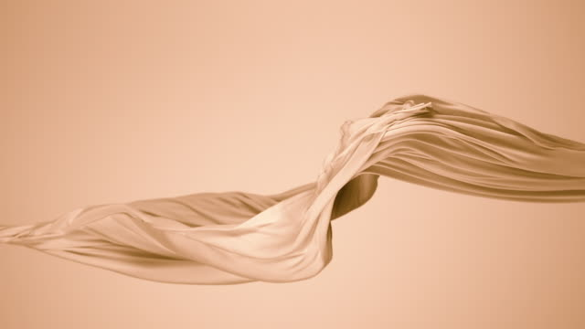vídeos de stock, filmes e b-roll de beige silky fabric flowing by wind in beige background, slow motion - dobrando