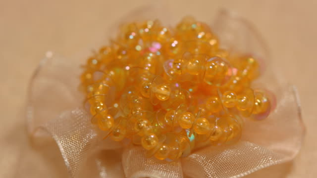 beige tissue flower decorated with amber beads - hair accessory stock videos & royalty-free footage