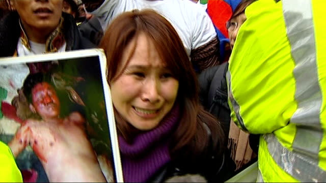 london torch procession disrupted by tibet protesters female protibet protester holding up photograph of bloodcovered tibetan and screaming her... - flaming torch stock videos & royalty-free footage