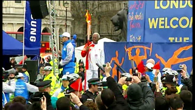 beijing 2008 olympic games: london torch procession disrupted by tibet protesters; trafalgar square: ext sir trevor mcdonald holding torch - 2008年北京夏季オリンピック点の映像素材/bロール