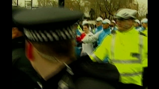 beijing 2008 olympic games: london torch procession disrupted by tibet protesters; police officers and torch attendants surrounding torch carrier... - water pistol stock videos & royalty-free footage
