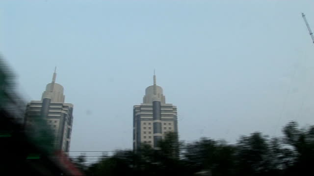 man evicted from house to make way for olympics china beijing ext skyscrapers and modern office buildings seen from travelling vehicle / yu shi liu... - 掘建て小屋点の映像素材/bロール