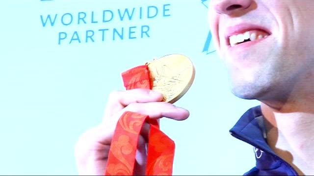 beijing 2008 olympic games: michael phelps in london; shot of phelps' feet phelps posing with gold medal phelps wearing gold medal phelps sitting in... - 2008年北京夏季オリンピック点の映像素材/bロール
