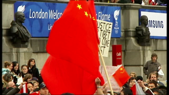 olympic torch procession celebrations and protests on trafalgar square and whitehall * * music heard during the following shots sot * * protibet... - olympic torch stock videos & royalty-free footage
