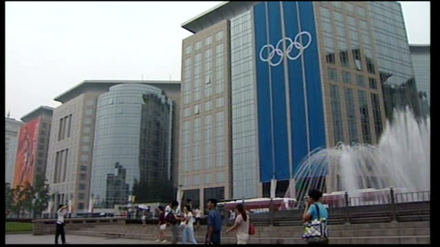 city building decorated with long red banner 'beijing 2008' to blue olympic rings banner on another building olympic banner seen beyond fountain in... - 2008年北京夏季オリンピック点の映像素材/bロール