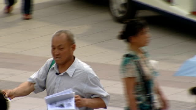beijing olympic games 2008: anti-smoking campaigner; more of zhang yue approaching people, giving out leaflets and taking their cigarettes away from... - 2008年北京夏季オリンピック点の映像素材/bロール